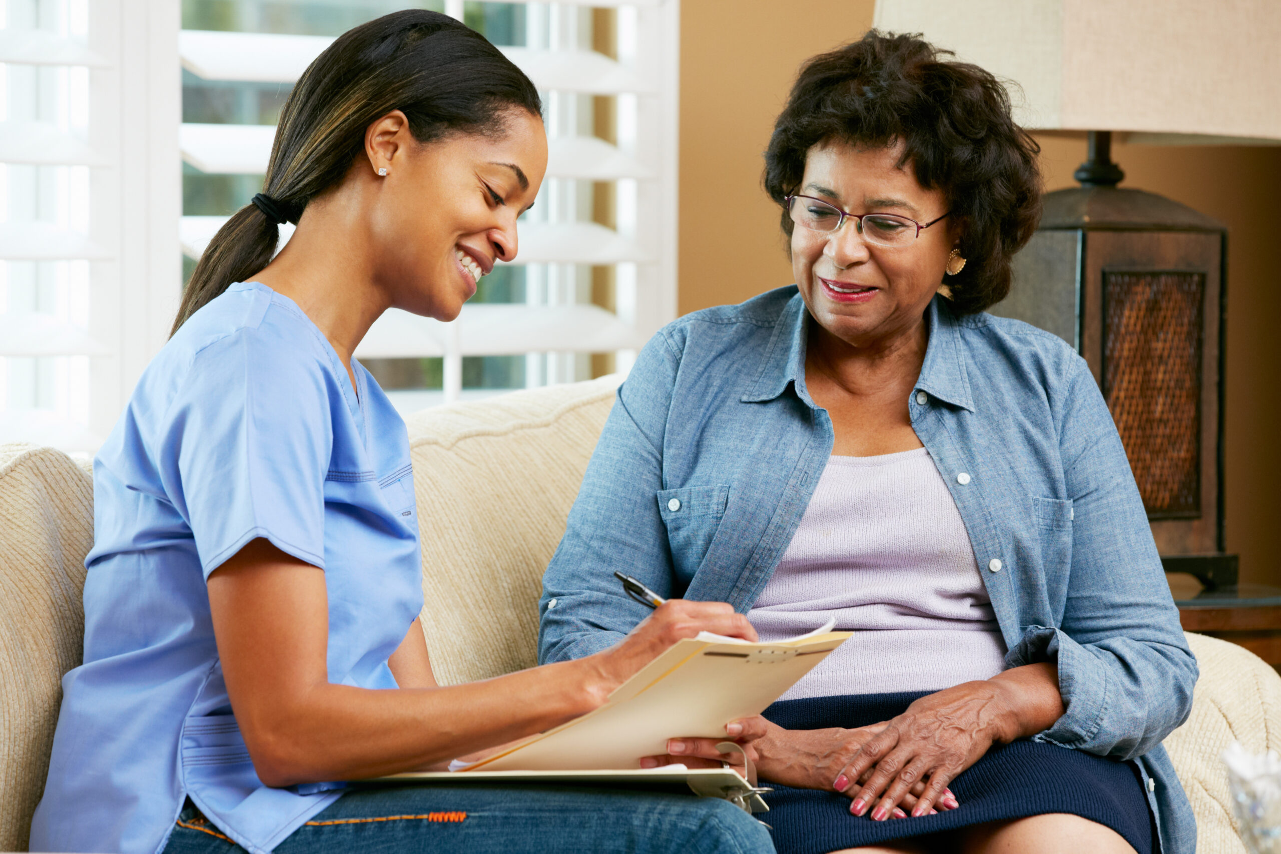 African-American nurse taking notes during visit with African-American patient